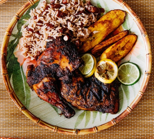 Jerk chicken, rice and plantain on bamboo plate